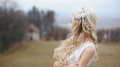 Beautiful stylish blonde bride with windy long hair posing at the blurred castle Stock Footage