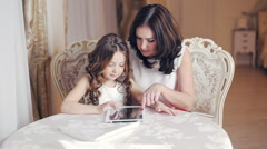 Mom and daughter are working with the tablet Stock Footage