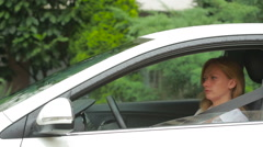 Woman get into the car in the rain. wear seat belts Stock Footage