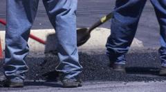 Close up of asphalt street paving with men shoveling tar Stock Footage