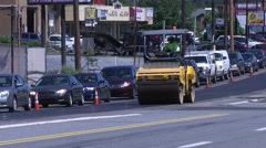 Steam Roller smooth out new asphalt street with traffic in other lane Stock Footage
