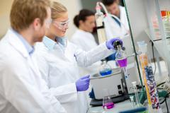 Female chemical technician mixing fluids in laboratory Stock Photos