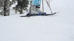 Young skier trying to go on the slope at a ski resort in the mountains in Stock Footage