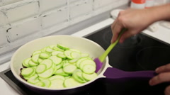 Frying fresh vegetable marrow in pan in domestic kitchen, female hands close-up Stock Footage