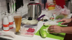 Female person cooking in the domestic kitchen and drinking beer from glass Stock Footage