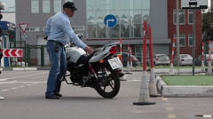 Driver instructor shows how to get motorcycle in parking lot. Russia Stock Footage