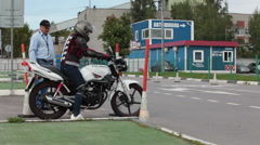 Young woman motorcyclist listens the male instructor on skill training Stock Footage