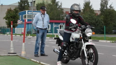 Woman motorcyclist and driving instructor are on driving school Stock Footage