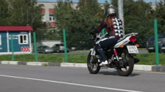 Young woman beginner rides on the motorbike on the skill training motordrom Stock Footage