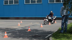 Beginner rides on the motorbike on the skill training. Instructor stands near. Stock Footage
