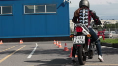 Beginner rides on the motorbike on the skill training motordrome Stock Footage