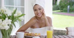Smiling woman wrapped in towel having breakfast Stock Footage