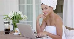 Beautiful woman in bath towel using laptop Stock Footage