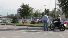 Driving instructor and L-driver motorcyclist are in driver training center.  Stock Footage