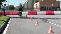 Learner motorcyclist tries to start driving on motorbike in motordrome Stock Footage