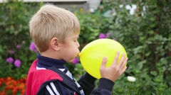 Child in the garden inflate a yellow balloon Stock Footage