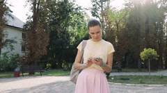 Pretty young woman in a pink skirt and a yellow T-shirt uses a smart phone Stock Footage