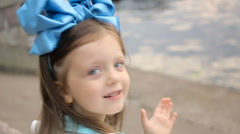 Portrait of a little girl three years with the blue bow on her head, which is Stock Footage