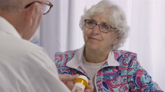 Senior woman happy to receive pills from her Doctor Stock Footage
