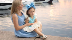 Little girl three years sitting on the lap of the mother with long blond hair Stock Footage