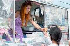 Lady with red hair wearing spotted apron serving ice cream Stock Photos