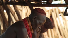 Medium Shot of Two Omo Valley Tribe Members Working In Their Hut Stock Footage