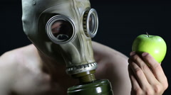 Naked man in a gas mask holding green Apple Stock Footage