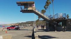 Lifeguards Jog Under Lifeguard Tower- La Jolla California Beach Stock Footage
