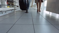 Down view of couple walking down airport hall Stock Footage