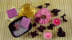 Spa Concept with flowers,beauty salt,massage oil and candle on bamboo background Stock Footage