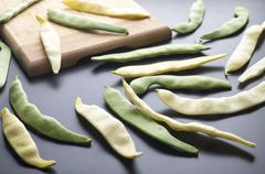 Yellow and green beans on a cutting board black table. Stock Photos