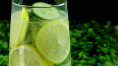 Fresh drink with lemon and cucumber slices in glass Stock Footage