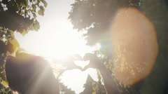 Girl park heart hands light flares sun Stock Footage