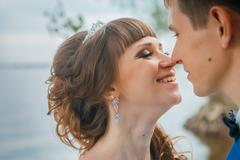 Bride and groom standing kissing in the background of the nature Stock Photos