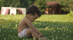 Happy Afro-American little girl learning to walk on the green grass Stock Footage