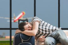 Delayed aeroplane concept. Tired passenger is sleeping on luggage in airport - stock photo
