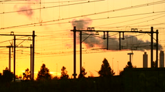 Yellow train riding through the trees at dusk. Smoking funnels from a factory Stock Footage