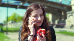 Happy girl chatting on cellphone and looking on bitten apple Stock Footage