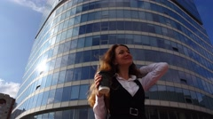 Girl in formal dress stand against high rise building with coffee at break time Stock Footage