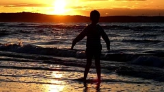 Little Boys Rise Hands Into the Sky Standing in the Sea During Sunset. Slow Stock Footage
