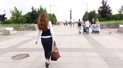 Young woman with brown handbag confidently go on wide parkway, follow shot Stock Footage