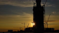 Sunset timelapse, bright sun move over tall tower construction, shine through Stock Footage