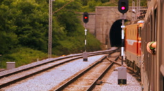 Passenger train in motion going towards the tunnel in the rural environment Stock Footage