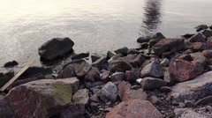 Tilt up from large granite stones on bay bank, tower construction on other side Stock Footage