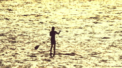 Woman silhouetted doing stand up paddle in the open sea at sunset 100p Stock Footage