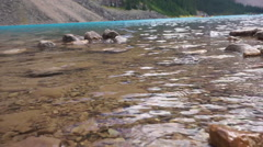 Beautiful lake, clear water with blur of people canoeing  on background Stock Footage