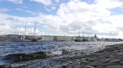 Small waves splash at stony embankment, sailboats moored at water area Stock Footage