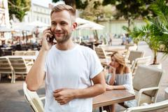 Man speaking on phone while his girlfriend being bored Stock Photos