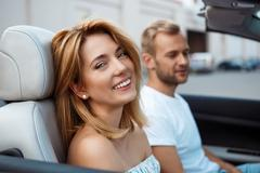 Young beautiful couple smiling, sitting in car near seacoast Stock Photos