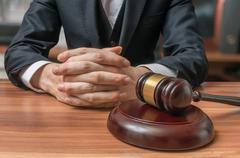 Lawyer has clasped hands and gavel in front. Justice and Law concept. Stock Photos